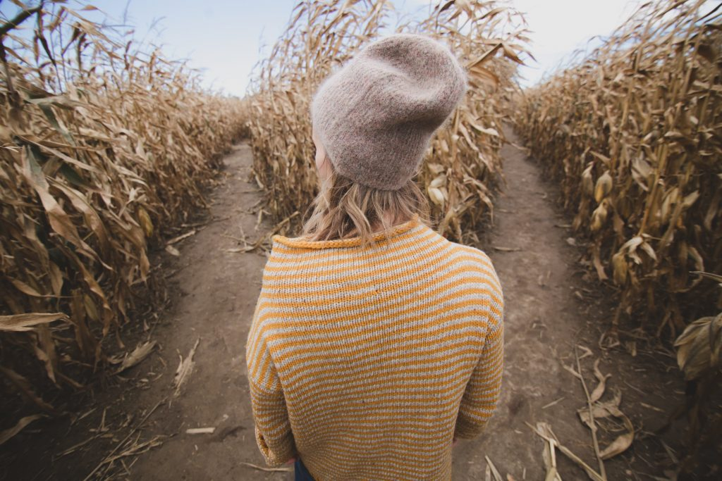 Woman standing at a fork in two paths through a wheat field