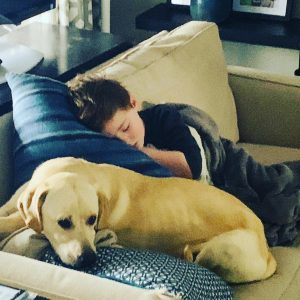 Dealing with Bored Kids: My son, Garrett, having a nap on top of our dog Summer.