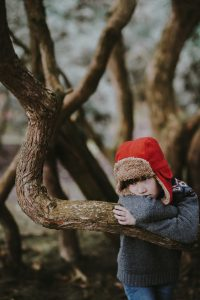 Kids are bored - child with red hat leaning against a tree and looking bored.