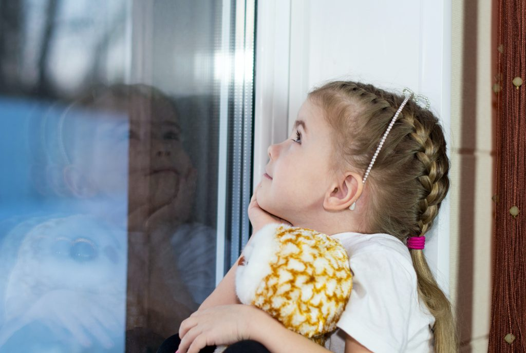 Little girl with braided hair, holding a stuffed animal, and looking out the window while daydreaming. She has a smile on her face.