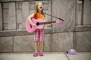 Kids Need Money: little girl with long red hair in pink plaid long shorts, singing and playing her pink guitar