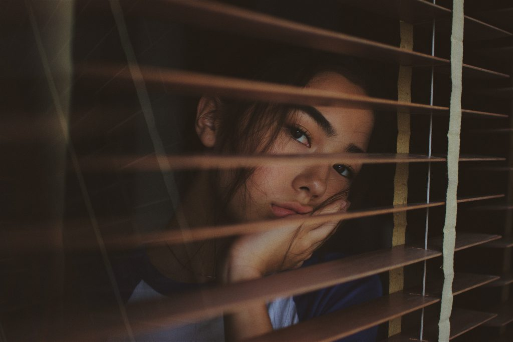 Kids are bored. Girl standing a window with blinds, looking out. She looks bored and sad.