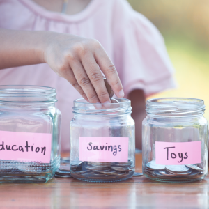 Kidpreneur Business Is a Real Think: Child putting coins into 3 different jars each labelled savings, toys, and education