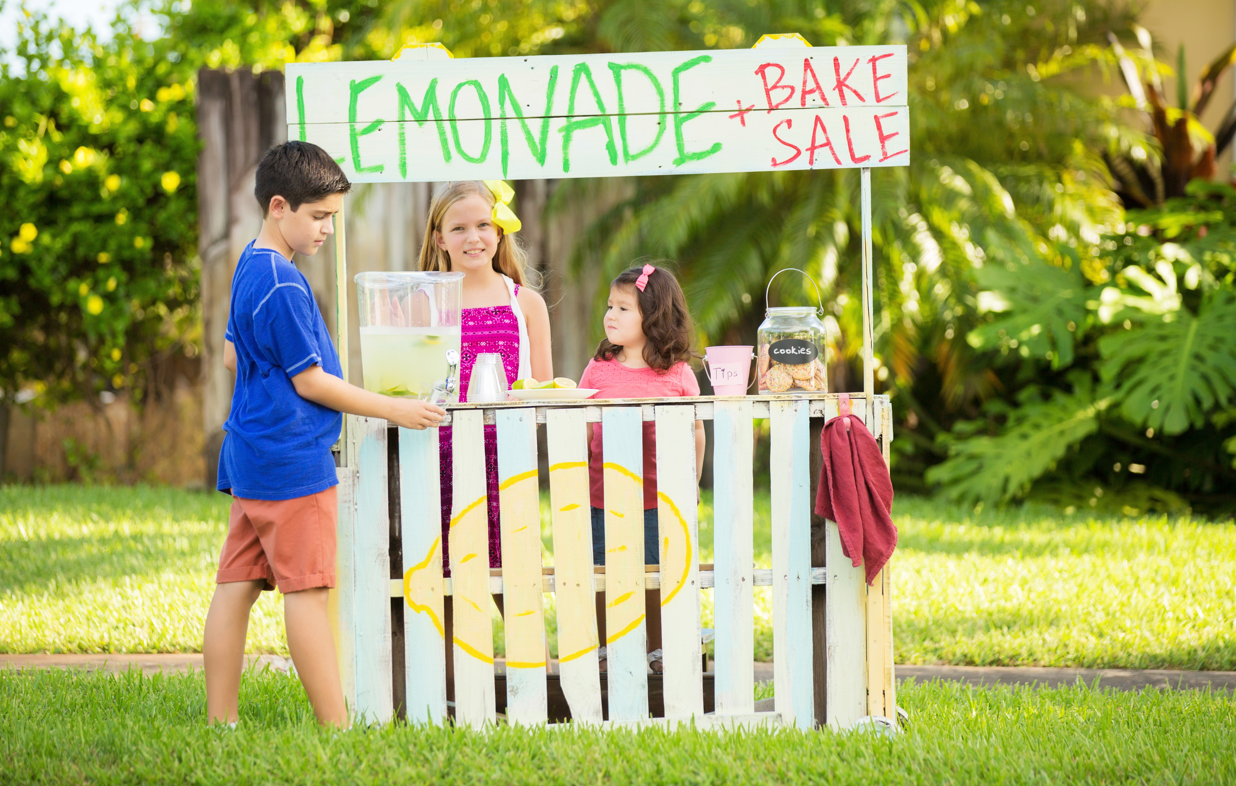 Kids' Business Ideas: Kids stand at a homemade lemonade stand. Sign above says lemonade and bake sale. Cookies and lemonade sit on the counter.