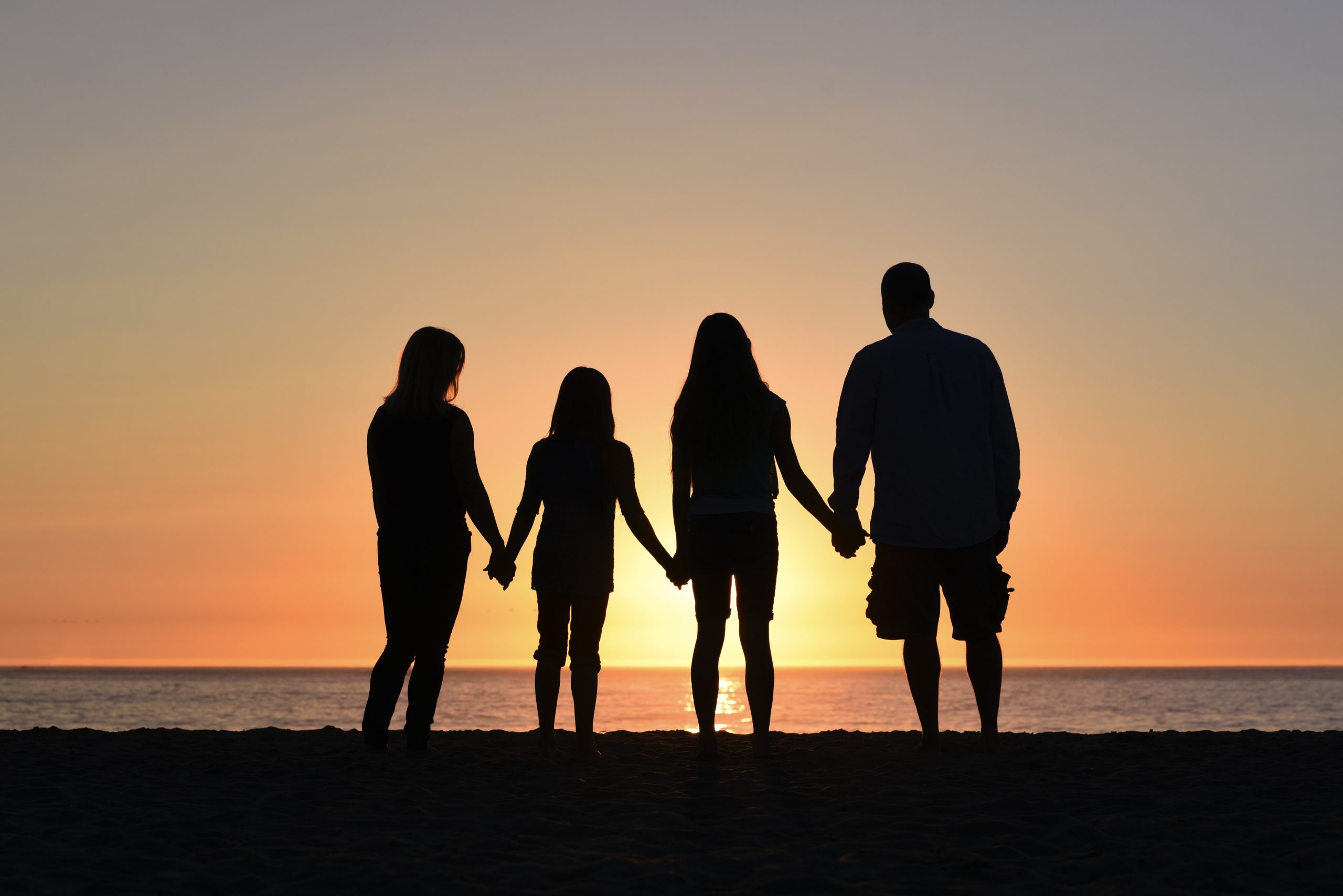 Build a close family for tomorrow; shows 2 adults and 2 kids (a family) holding hands and watching the sunsight. They are shown in silhouette.