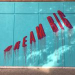 graffiti like street sign that says Dream Big painted in bold red letters