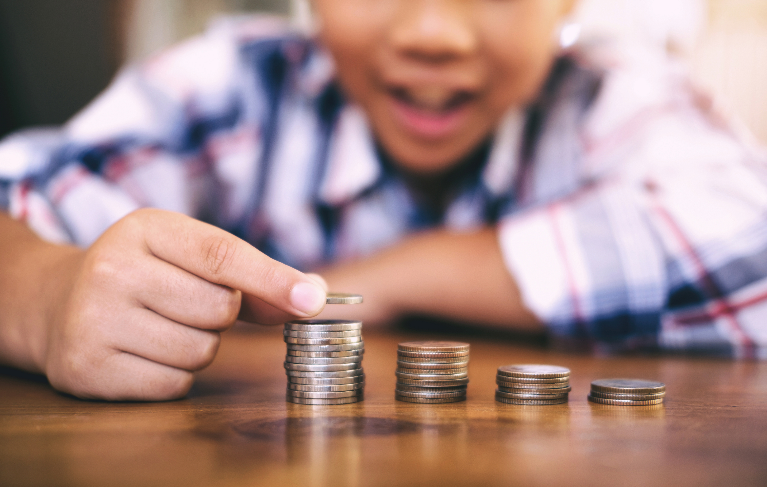 It's Allowance Day - Child counting out coins on the table in front of him