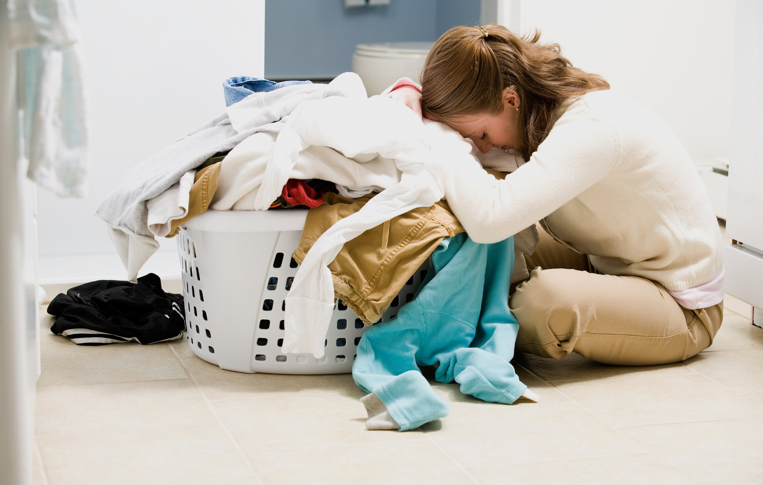 Overwhelmed Mom - a woman sits on the floor with her face buried in a pile of laundry looking overwhelmed.